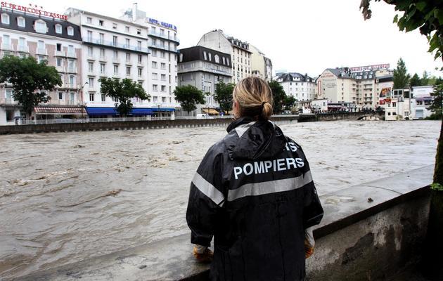 Une femme sapeur-pompier regarde la crue du Gave à Lourdes, le 18 juin 2013  [Laurent Dard / AFP]