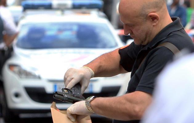 """Un policier collecte une arme devant la bijouterie """"La Turquoise"""" le 11 septembre 2013 à Nice  [Jean-Christophe Magnenet  / AFP]"""