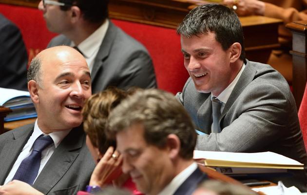 Pierre Moscovici (g) se retourne à l'Assemblée pour parler à Manuel Valls (d) le 17 septembre 2013 [Eric Feferberg / AFP]