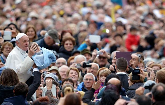 Le pape prend un bébé dans ses bras lors d'un bain de foule à son arrivée à Saint-Pierre, le 13 novembre 2013 au Vatican [Alberto Pizzoli / AFP/Archives]