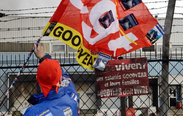 Un salarié agite un drapeau de la CGT devant l'usine Goodyear d'Amiens, le 5 décembre 2013, après l'annonce de la fermeture du site [Denis Charlet / AFP/Archives]