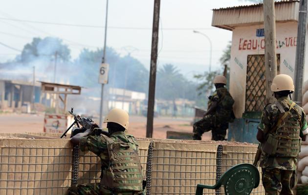 Des soldats rwandais de la Misca regardent une maison brûler à Bangui, le 9 février 2014 [Issouf Sanogo / AFP]