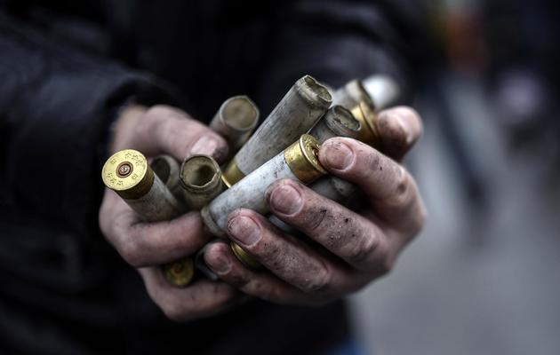 Un manifestant montre des cartouches vides utilisées par le police anti-émeute à Kiev le 20 février 2014 [Bulent Kilic / AFP]