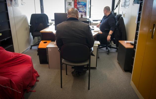Un policier de l'Ocriest écoute un suspect dans le cadre d'une enquête sur un trafic de pièces d'état-civil à Lognes le 3 mars 2014 [Martin Bureau / AFP]