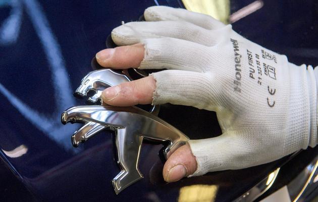 Un employé de PSA Peugeot Citroën positionne le logo du constructeur sur une 308, sur une chaîne d'assemblage à Sochaux en mars 2014  [Sébastien Bozon / AFP/Archives]