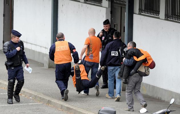 Des policiers, vêtus de gilet orange fluo, amènent deux mannequins figurant les victimes pour la reconstitution le 3 avril 2014 à Echirolles de la mort de Kevin et Sofiane [Jean-Pierre Clatot / AFP]