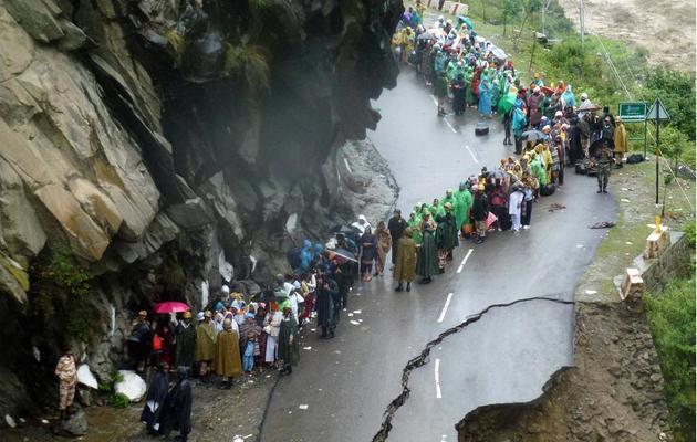 Des habitants bloqués par les inondations sur une route à Chamoli le 18 juin 2013 dans l'état d'Uttarakhand [ / Armée indienne/AFP]