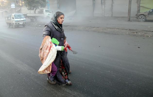 Une Syrienne blessée marche avec ses deux enfants après des raids de l'armée de l'air à Alep, le 15 décembre 2013 [ / Mohammed Al-Khatieb/AFP]