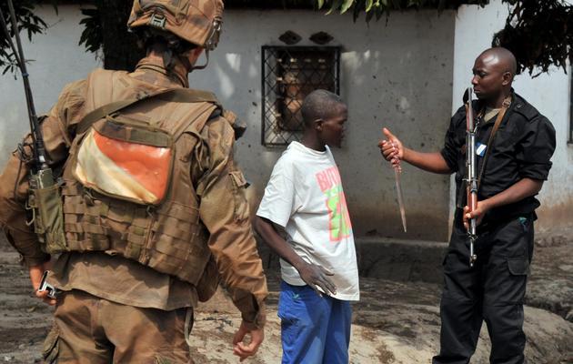 Un soldat français de l'opération Sangaris et un gendarme centrafricain confisquent un couteau à un homme, le 9 février 2014 à Bangui [Issouf Sanogo / AFP]