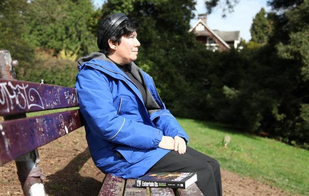 Gillian Gaar, auteur d'un livre sur Nirvana, assise sur le banc couvert de graffiti qui fait figure de monument funéraire pour le chanteur Kurt Cobain, photographiée à Viretta Park à Aberdeen, le 1er avril 2014 [Sebastian Vuagnat / AFP]