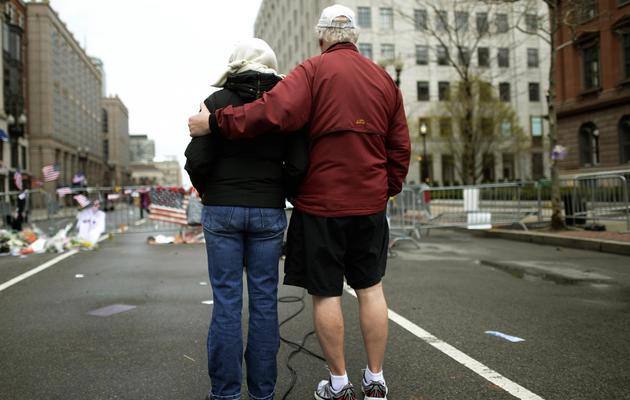 Deux personnes se recueillent le 20 avril 2013 à Boston après les attentats qui avaient endeuillé le célèbre marathon [Timothy  A.Clary / AFP]