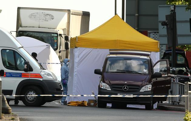Experts et policiers le 22 mai 2013 à Londres à l'endroit où un soldat a été tué à l'arme blanche [Leon Neal / AFP]