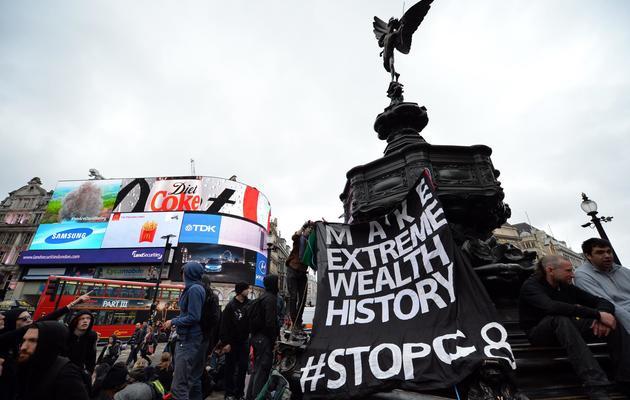 Des manifestants opposés au sommet du G8 occupent la place de Piccadilly Circus, le 11 juin 2013 à Londres [Leon Neal / AFP]