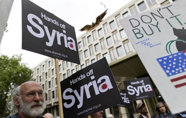 Des manifestants brandissent des pancartes pour demander à l'Occident de ne pas s'impliquer dans le conflit syrien, devant l'ambassade américaine à Londres, le 15 juin 2013 [Justin Tallis / AFP]