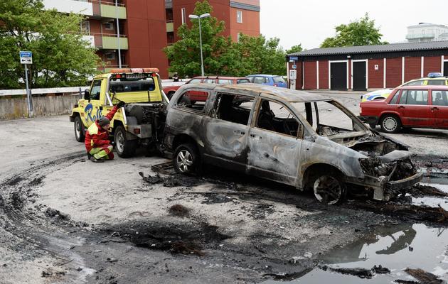 Une voiture incendiée lors des émeutes à Husby, un quartier du nord de Stockholm, est évacuée le 21 mai 2013 [Jonathan Nackstrand / AFP]
