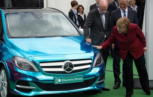 Angela Merkel contemple une Mercedes E-drive, le 27 mai 2013 à Berlin [Johannes Eisele / AFP]