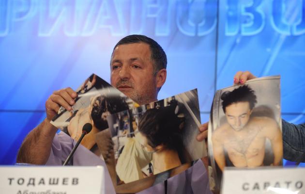 Abdoulbaki Todachev montre le 30 mai 2013 à Moscou les photos du cadavre de son fils Ibraguim Todachev, tué par le FBI [Andrey Smirnov / AFP]