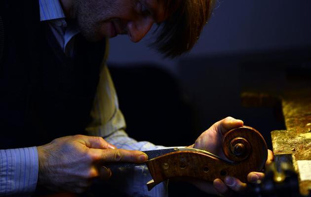 Le luthier français Mathias Menanteau en train de restaurer un violoncelle dans son atelier à Rome, le 30 janvier 2013 [Gabriel Bouys / AFP]