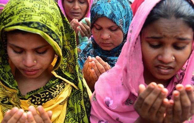 Des femmes prient le 14 mai 2013 lors d'un hommage aux victimes de l'effondrement de l'immeuble près de Dacca, qui a fait  près de 1200 morts [Munir Uz Zaman / AFP]