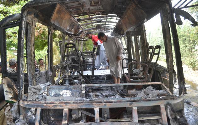 Un homme inspecte un autocar d'université détruit par une attaque à la bombe à Quetta le 15 juin 2013 [Banaras Khan / AFP]