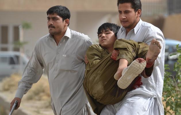 Un Pakistanais transporte un enfant blessé après une attaque contre un hôpital à Quetta le 15 juin 2013 [Banaras Khan / AFP]