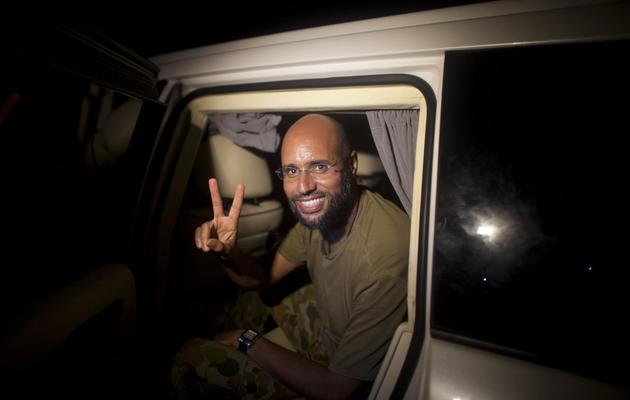 """Seif al-Islam Kadhafi fait le signe de la victoire devant des partisans de l'ancien """"guide"""" libyen et des journalistes, le 23 août 2011 à Tripoli [Dario Lopez-Mills / Pool/AFP/Archives]"""