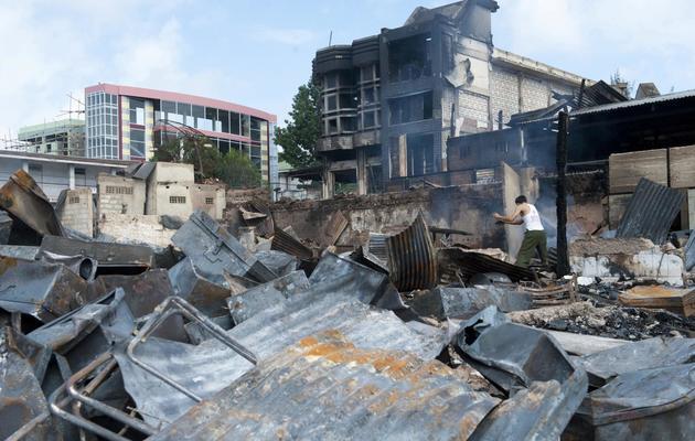 Un homme commence à déblayer un marché brûlé lors de violences religieuses à Lashio, le 30 mai 2013 [Ye Aung Thu / AFP]