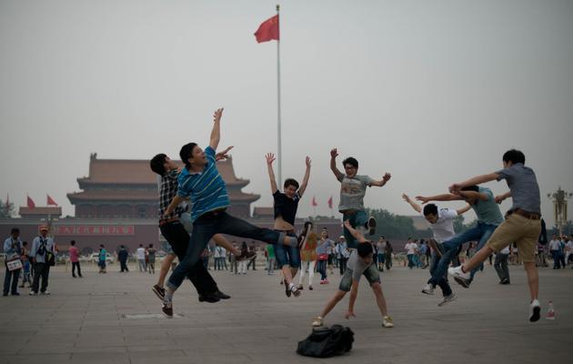 Des touristes sautent en l'air pendant que leurs amis les prennent en photo sur la place Tiananmen à Pékin, le 4 juin 2013 [Ed Jones / AFP]