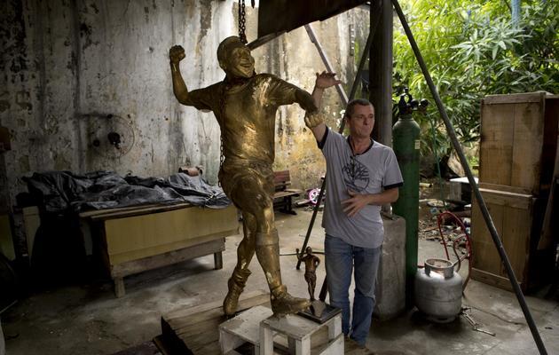 Le sculpteur et caricaturiste Ique et sa statue de Pelé, dans son atelier de Rio de Janeiro, le 22 janvier 2013. [Christophe Simon / AFP]