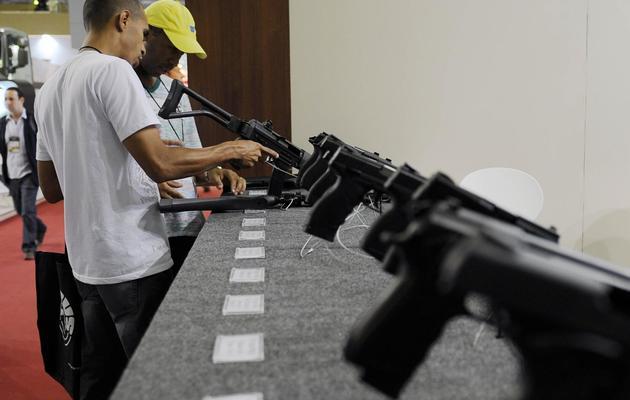Deux hommes inspectent des armes au Salon de la Défense et de la Sécurité (LAAD), à Rio de Janeiro le 9 avril 2013 [Vanderlei Almeida / AFP]