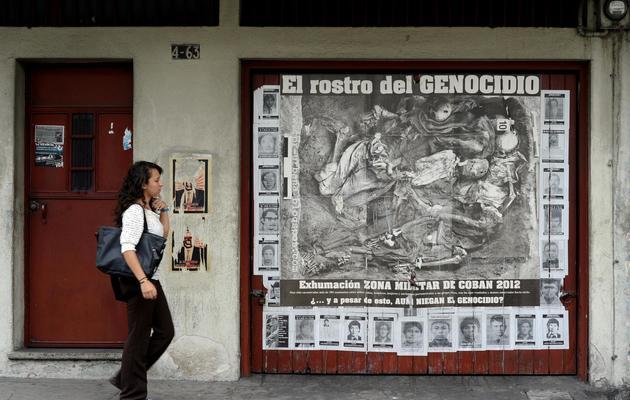 """Une femme marche, le 21 mai 2013 à Guatemala City, devant un mur couvert de portraits de """"disparus"""" [Johan Ordonez / AFP]"""