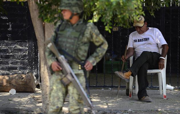 Un homme dort derrière un soldat mexicain à Tepacalcatepec, dans l'Etat du Michoacan, le 22 mai 2013 [Alfredo Estrella / AFP]