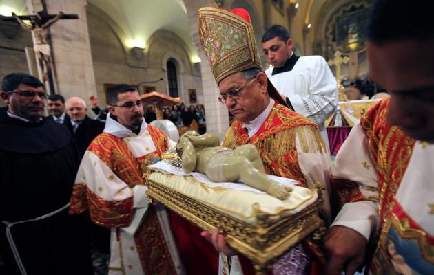 Le patriarche latin de Jérusalem, Mgr Fouad Twal, porte une réplique de l'enfant Jésus, à Bethléem, le 25 décembre 2012 [Abed al-Hashlamoun / Pool/AFP]