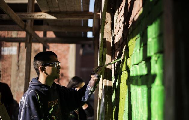 Le jeune Diaa el-Sayyed occupé à peindre un mur, au Caire, le 19 janvier 2013 [Gianluigi Guercia / AFP]