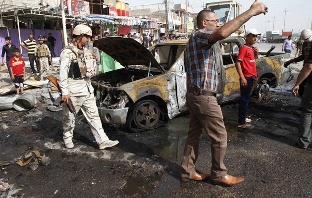 Des Irakiens devant un voiture brûlée après un attentat à la voiture piégée, le 20 mai 2013 à Bassora dans le sud du pays [Ramzi al-Shaban / AFP]