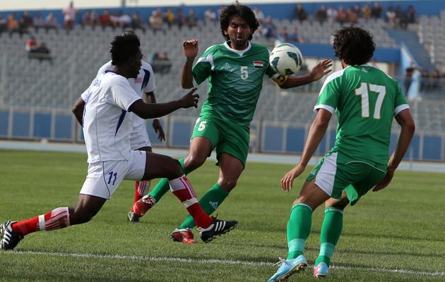 Hamam Tarik du Liberia (g) à la lutte avec l'Irakien Nashat Akram lors d'un match amical à Bagdad le 27 mai 2013, juste avant un attentat [Ahmad al-Rubaye / AFP]