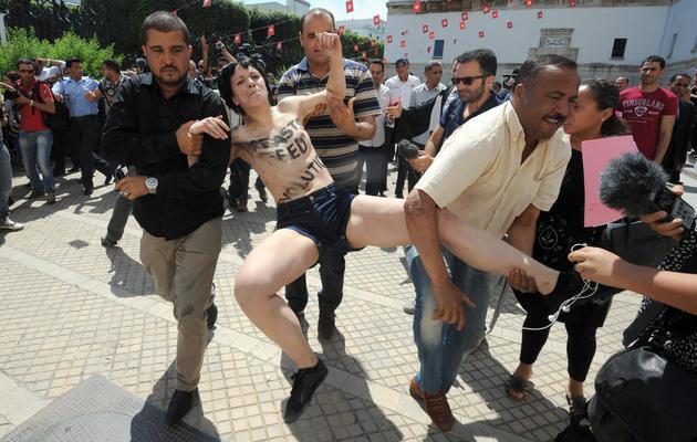 Les forces de sécurité interpellent l'une des militantes Femen, le 29 mai 2013 à Tunis [Fethi Belaid / AFP]