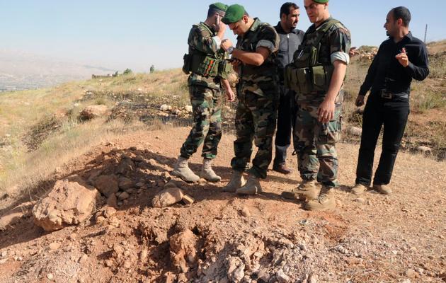 Des soldats constatent les cratères laissés par une roquette tirée depuis la Syrie, atteignant la région de la Bekaa, au Liban, le 1er juin 2013 [ / AFP]