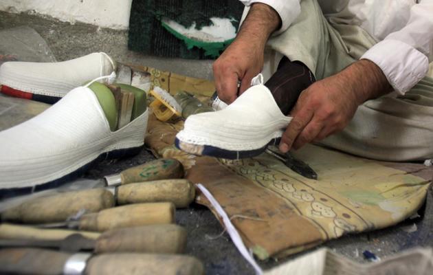 """Un Kurde essaie une """"klash"""", la traditionnelle espadrille kurde, dans un atelier à Halabja, au Kurdistan irakien, le 16 mars 2013 [Ali al-Saadi / AFP]"""