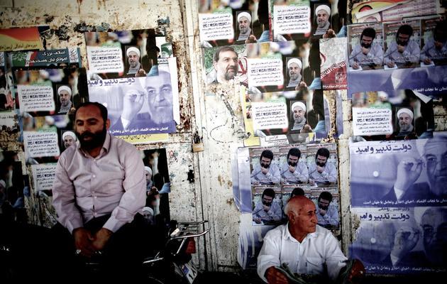 Des Iraniens devant des affiches en faveur de Hassan Rohani (g) et Mohsen Rezai (c), le 9 juin 2013 à Téhéran [Behrouz Mehri / AFP]