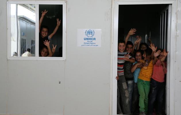 Des enfants syriens à l'entrée de leur salle de classe, dans le camp de réfugiés de Domiz, en Irak [Safin Hamed / AFP]