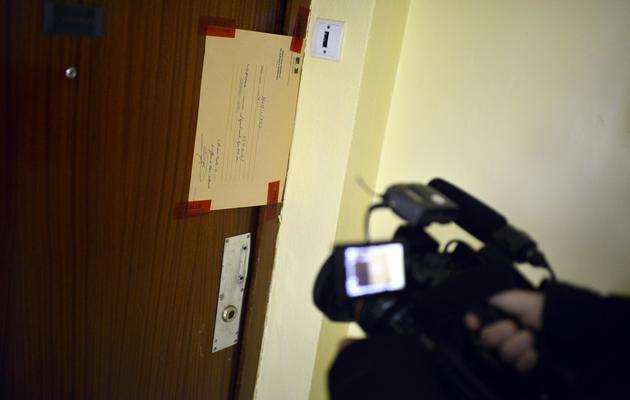 Un journaliste filme à Saint Priest, près de Lyon, les scellés laissés par la police sur la porte d'un appartement où un père est soupçonné d'avoir tué ses enfants, le 19 mai 2013 [Jeff Pachoud / AFP]