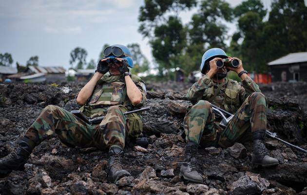 Deux casques bleus de la mission des Nations unies en RDC observent aux jumelles les déplacements de rebelles du M23, le 18 novembre 2012 [Phil Moore / AFP/Archives]