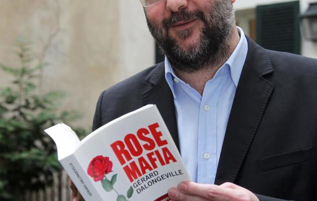 """L'ancien maire d'Hénin-Beaumont, Gérard Dalongeville, pose avec son livre """"Rose Mafia"""", à Paris, le 23 février 2012 [Pierre Verdy / AFP/Archives]"""