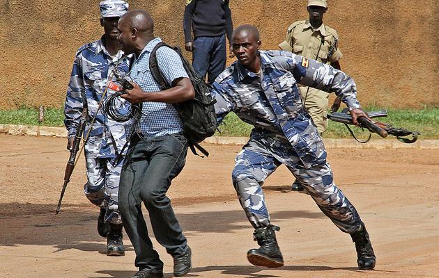 Des policiers ougandais arrêtent un journaliste, le 28 mai 2013 à Kampala [Isaac Kasamani / AFP]