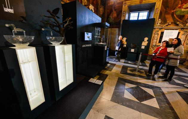 Des visiteurs devant une représentation de la théorie des vases communicants, présentée lors de l'exposition sur Archimède, le 30 mai 2013 à Rome [Andreas Solaro / AFP]