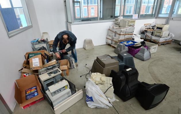 Un ancien employé de la société Maflow, située près de Milan, inspecte le 16 mai 2013, des anciens composants électroniques pour les recycler [Giuseppe Cacace / AFP]