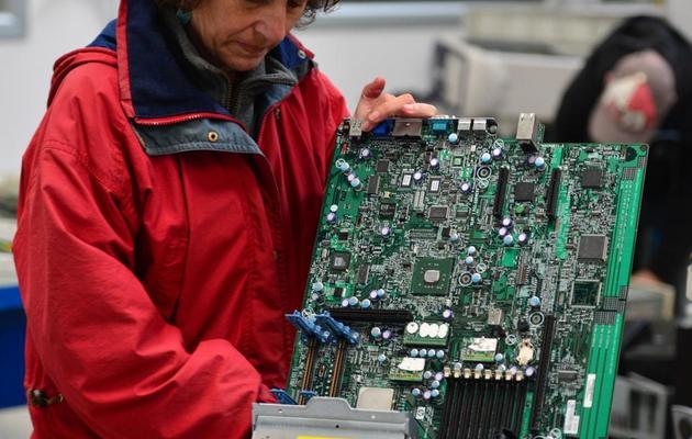 Une ancienne employée de la société Maflow récupère du matériel électronique, le 16 mai 2013, dans l'usine occupée près de Milan [Giuseppe Cacace / AFP]