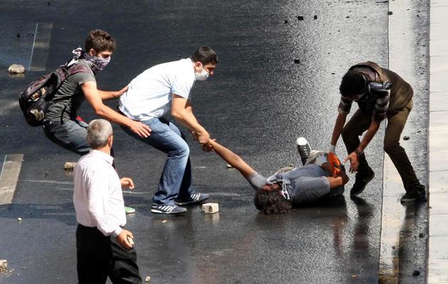 Des manifestants aident un blessé à se relever, en marge des manifestations, à Ankara, le 1er juin 2013 [Adem Altan / AFP]
