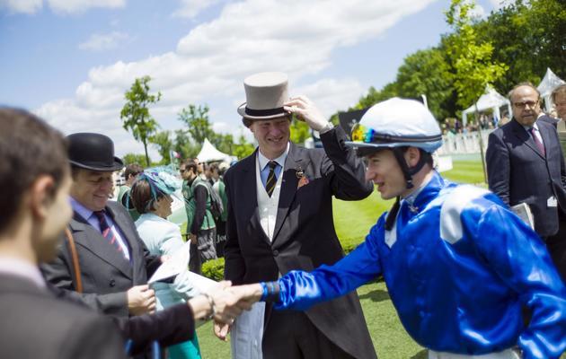Des spectateurs saluent un jockey au prix du Jockey Club à Chantilly le 2 juin 2013 [Fred Dufour / AFP]